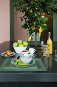Charcoal-grey island counter used as breakfast table with decorative lemon tree planted in centre