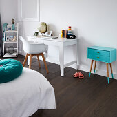 White desk, shell chair and turquoise chest of drawers in child's bedroom