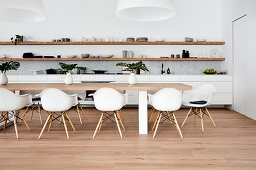 Long white kitchen counter below wooden shelves and dining table with shell chairs