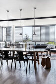 Long dining table and chairs below pendant lamps with outdoor lounge in background