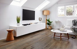 Low sideboard, TV on wall, standard lamp, sofa and coffee table in attic living room