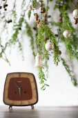 Larch branches decorated for Christmas above vintage alarm clock on table