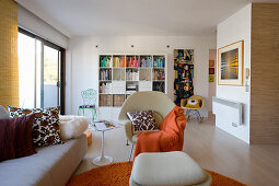 Sofa, designer chairs, shelves and orange accents in open-plan interior