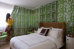 Double bed with rattan headboard, bedside cabinets and green armchair in bedroom - woman closing curtain