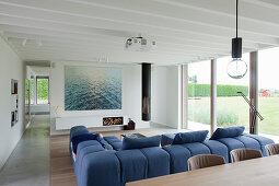 Modernes Wohnzimmer mit Fensterfront und blauem Sofa