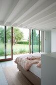 Blick vom Schlafzimmer mit Balkendecke in den Garten