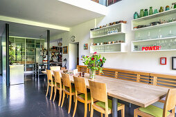 Dining area with wall-mounted shelves in high-ceilinged, open-plan interior