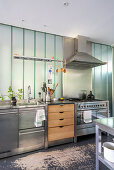 Island counter with stainless steel and wooden fronts below frosted glass wall