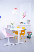 Esstisch in weißem Wohnraum mit knallbunten Farbakzenten