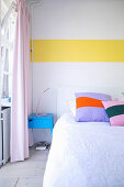 White bedroom wall with accent provided by horizontal yellow stripe