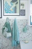 Netzbeutel mit Toilettenpapier und Handtuch im Badezimmer mit Mosaikfliesen