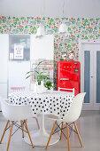 Essbereich, roter Kühlschrank und weißer Küchenschrank vor Blumentapete