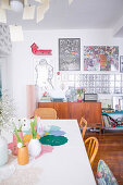 View past spring flowers on dining table to retro sideboard and glass-brick interior wall