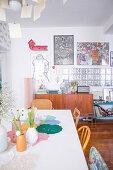 Blick über Esstisch mit Frühlingsblumen auf Retro Sideboard und Glasbausteine