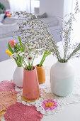 Vasen mit Frühlingsblumen und Häkeldeckchen auf Esstisch