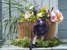 Summer bouquet of roses, grasses and lavender in basket in wreath of lavender