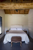 Double bed in simple bedroom with wooden ceiling beam