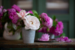 Pink and white roses in metal vase on wooden table