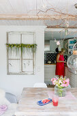 Watermelon and summer bouquet in dining room with woman in background in open-plan kitchen