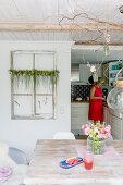 Esszimmer mit Wassermelone und Sommerstrauß, im Hintergrund Frau in offener Küche