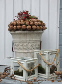 Wreath of walnuts on stone urn and candle lanterns