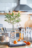 Fir branch in swing-top bottle. glasses and cutlery on tray behind tangerines on folded tea towels