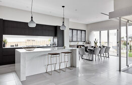 Kitchen counter with bar stools and dining area in open-plan interior with tiled floor
