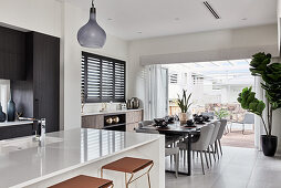 Kitchen counter with bar stools and dining area next to terrace doors in open-plan interior