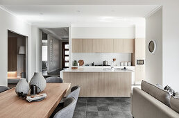 Dining area, sofa and kitchen in open-plan interior
