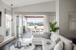 Pale sofa set with cushions and coffee table with view of roofed terrace in background