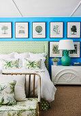 Bildergalerie mit Naturmotiven an leuchtend blauer Wand über Doppelbett