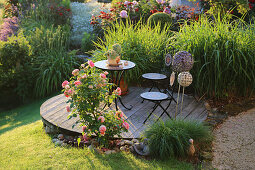 Table and chairs on wooden deck surrounded by roses and Chinese reeds in garden