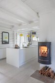 White island counter in kitchen and fireplace in foreground in white-painted log cabin