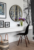 Round lattice mirror above desk and black chair