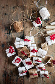 Small gifts with numbered, felt Christmas trees arranged and twine