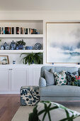 Upholstered sofa with cushions and seating cubes, large picture behind and shelves in alcove