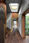 Hallway with skylight and wooden stairs