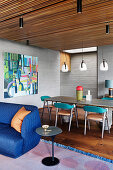 Blue sofa and side table, behind it dining table with chairs in an open living room with a wooden ceiling and concrete-look walls