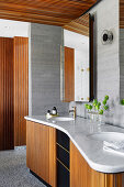 Double washbasin with marble top and wooden front in the bathroom with walls in concrete look
