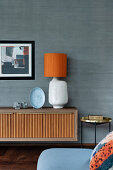 Lowboard with table lamp and side table against wooden wall in concrete look
