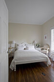White double bed with white bedspread in bedroom with dark wooden floor