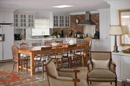 Kitchen with white cabinets and brick wall behind solid wooden dining table with chairs and two armchairs