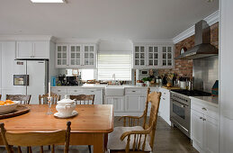 Kitchen with white cabinets and solid wooden dining table and chairs