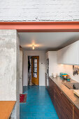 Elongated kitchen with bright blue floor tiles and concrete walls