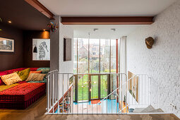 Sofa in lounge area on mezzanine and head of stairs leading down into open-plan interior