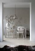 Open doorway leading into wintry dining room with white retro chairs