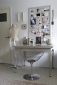 Transparent chair at grey console table below mood board on wall