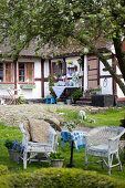 Wicker chairs in seating area in garden outside old half-timbered house