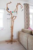 Lanterns hung from gnarled tree against back of sofa