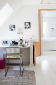 Desk below skylight and pictures of children on wall